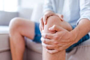 Image of man holding painful knee.