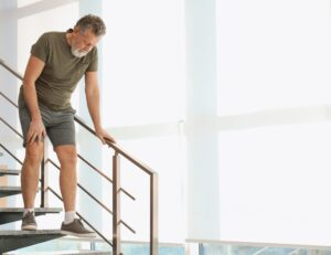 Image of older man walking carefully down a staircase.